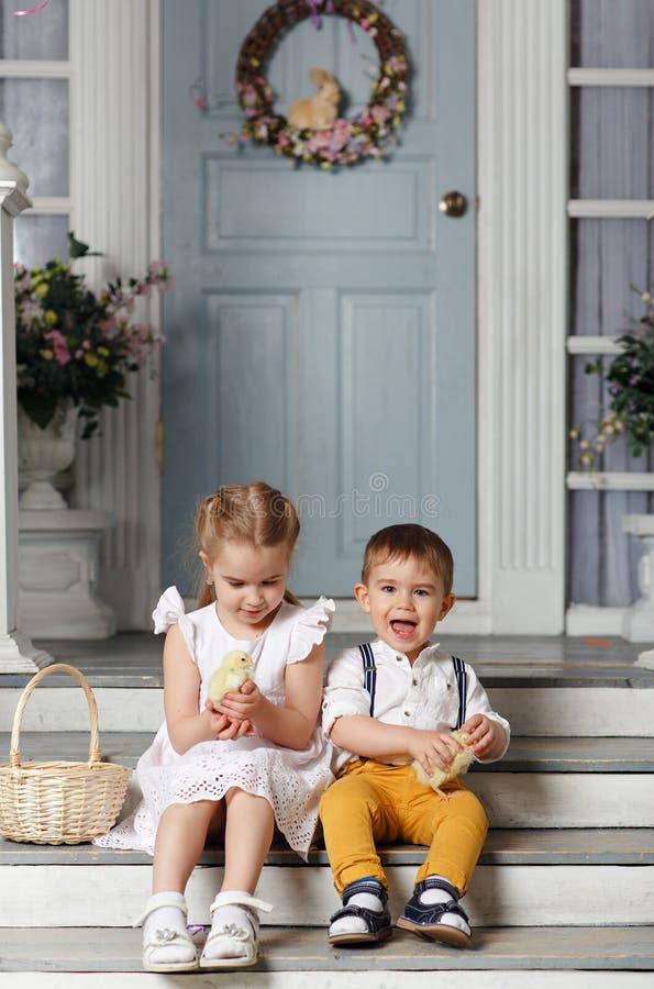 Мои сестра и младший брат сидя на лестницах дома и стоковые фото