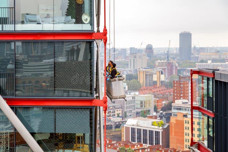 Мойщики окон работая на высоком здании подъема стоковое изображение rf