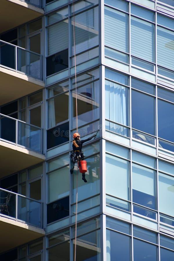 Мойщик окон очищая окно высокого здания подъема стоковое фото rf