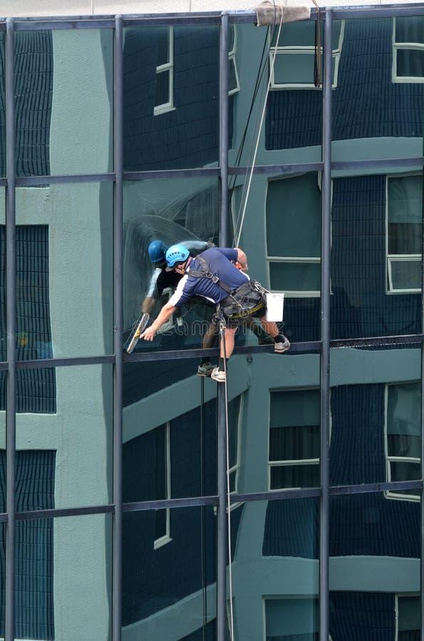 Мойщик окон работает на высоком здании подъема стоковая фотография
