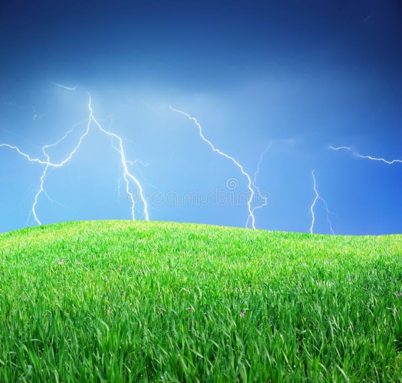 Молния и зеленый лужок стоковое изображение