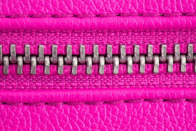 Молния металла на интенсивном розовом пурпурном кожаной конце детали куртки или портмона вверх по макросу Молния плотно закрыта стоковая фотография