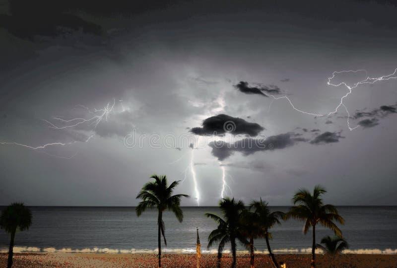 Молния охватывает небо и океанские волны лета ниже стоковое изображение
