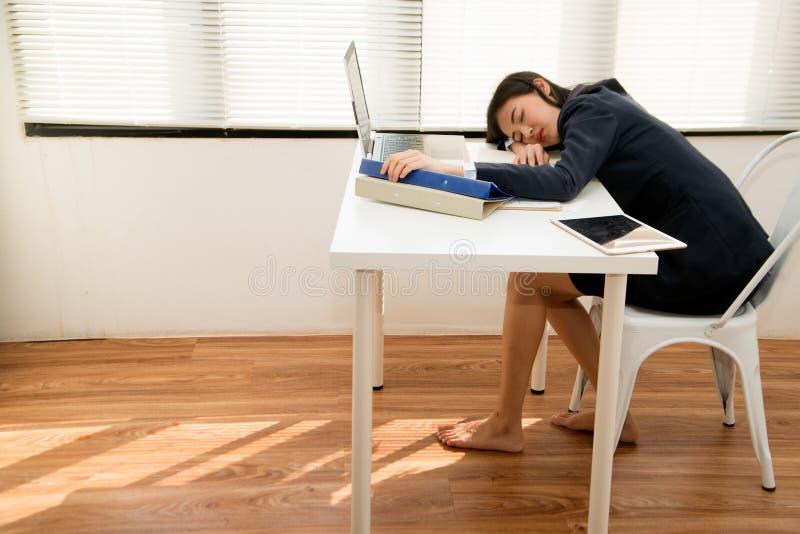 Молодая азиатская бизнес-женщина лежит на столе в офисе из-за уÑ'омиÑ'ÐµÐ»Ñ стоковая фотография
