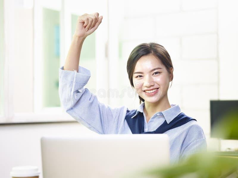 Молодая азиатская бизнес-леди развевая кулак стоковая фотография