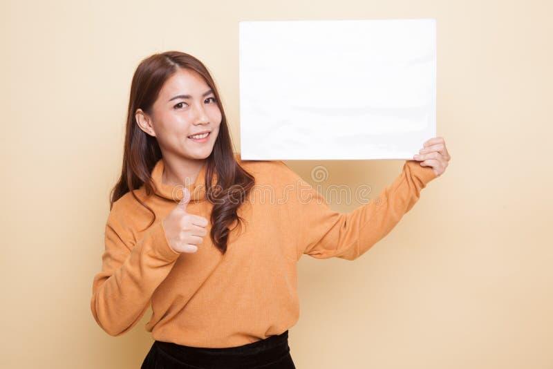 Молодая азиатская выставка женщины thumbs вверх с белым пустым знаком стоковое изображение rf