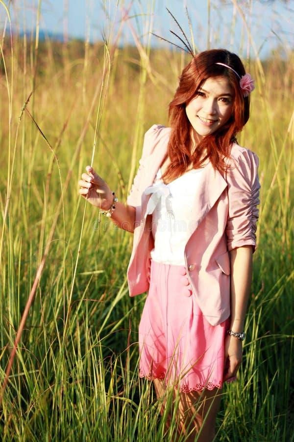 Молодая азиатская девушка в траве стоковое фото rf