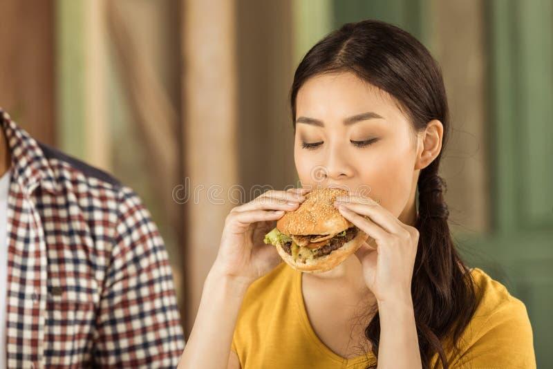 Молодая азиатская девушка есть вкусный бургер стоковая фотография