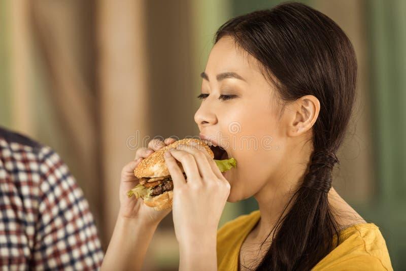 Молодая азиатская девушка есть вкусный бургер стоковые фото