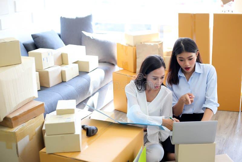 Молодая азиатская девушка начало фрилансера вверх по адресу сочинительства владельца мелкого бизнеса на картонной коробке на рабо стоковое фото rf