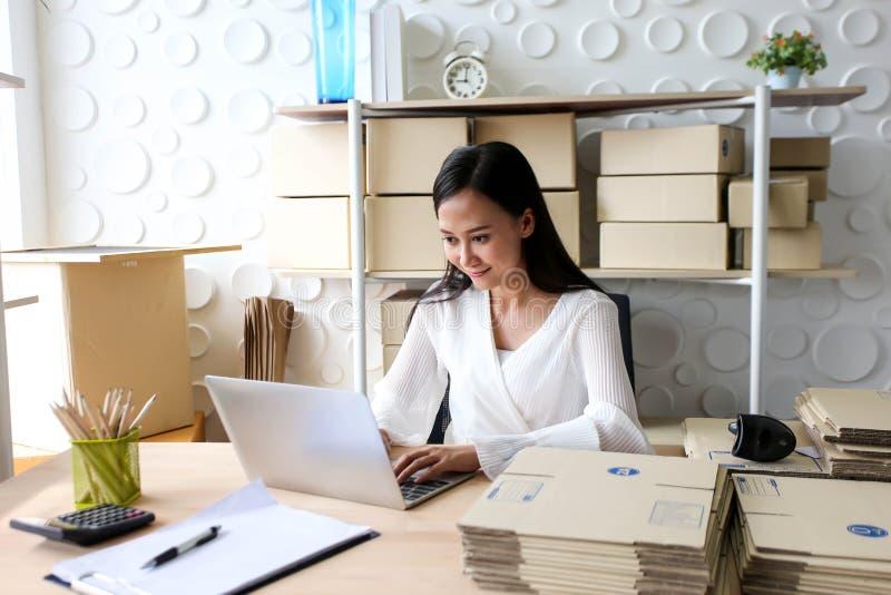 Молодая азиатская девушка начало фрилансера вверх по адресу сочинительства владельца мелкого бизнеса на картонной коробке на рабо стоковые фотографии rf