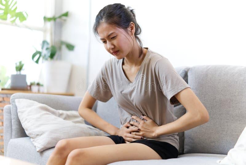 Молодая азиатская девушка на страдании софы от stomachache и иметь некоторую лихорадку из-за менструации стоковые изображения rf
