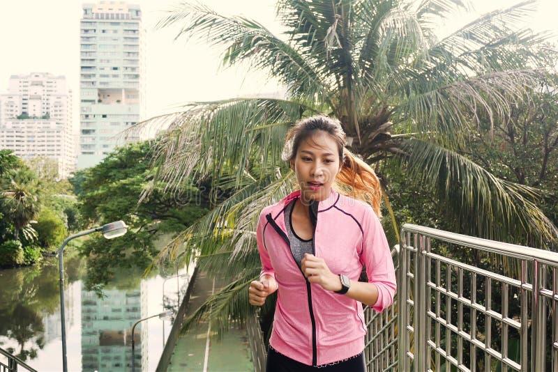 Молодая азиатская женщина бежать на тротуаре в утре Женщина молодого спорта азиатская бежать вверх на лестницах города стоковое фото