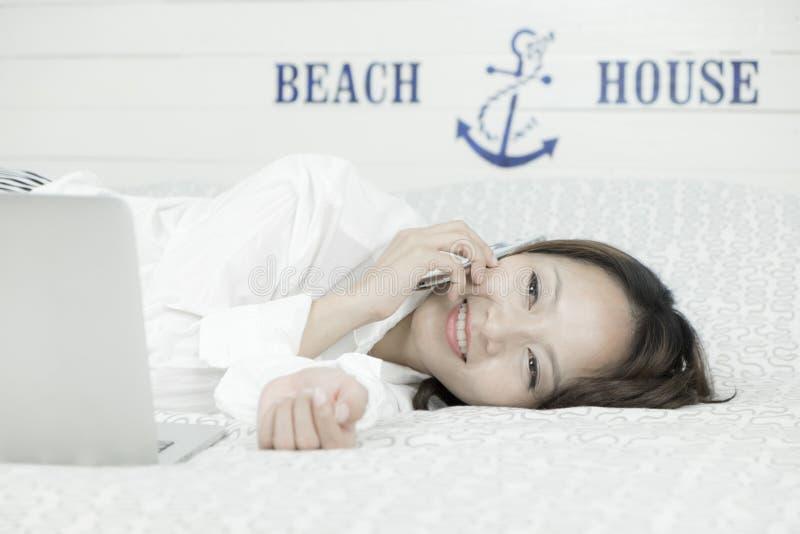 Молодая азиатская женщина говоря на телефоне пока кладущ на кровать стоковое фото