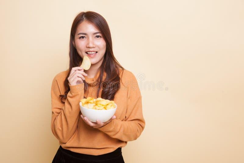 Молодая азиатская женщина ест картофельные стружки стоковое изображение rf