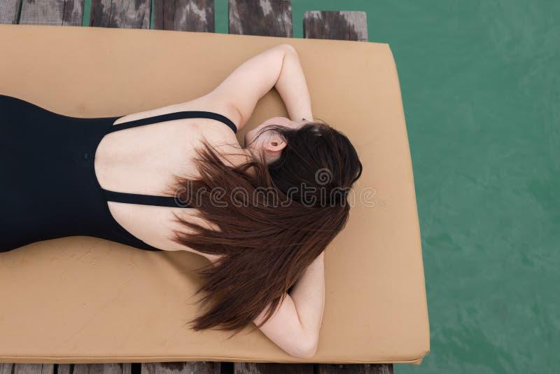 Молодая азиатская женщина загорает на пляже стоковая фотография