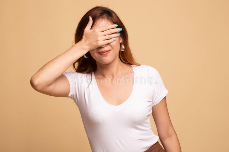 Молодая азиатская женщина закрыть ее глаза с рукой стоковое изображение rf