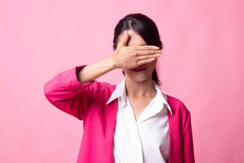 Молодая азиатская женщина закрыть ее глаза с рукой стоковое фото rf