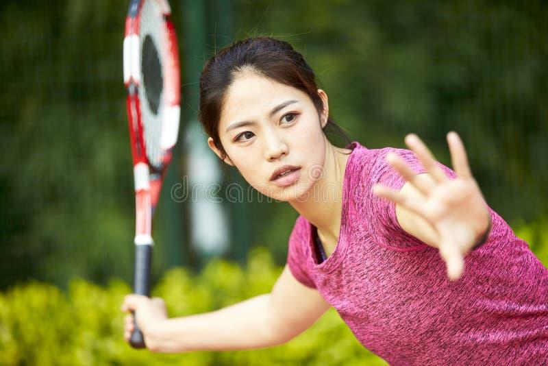 Молодая азиатская женщина играя теннис стоковые фото