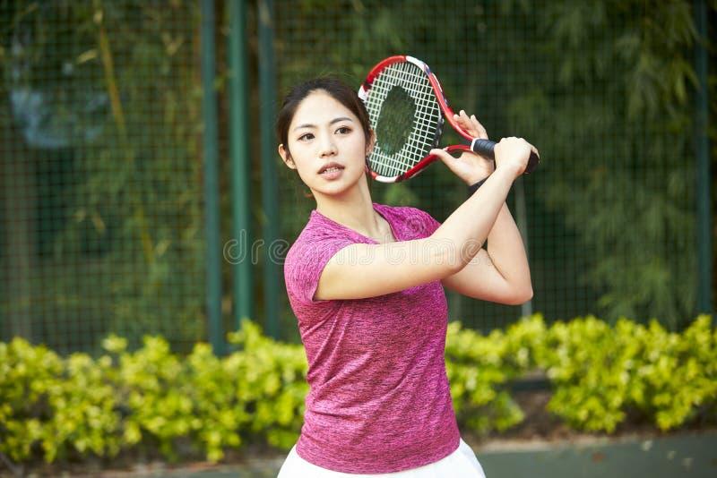 Молодая азиатская женщина играя теннис стоковое фото