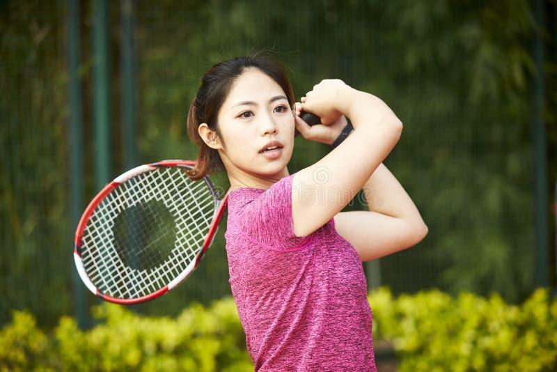 Молодая азиатская женщина играя теннис стоковые изображения