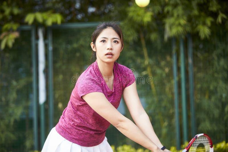 Молодая азиатская женщина играя теннис стоковые фотографии rf