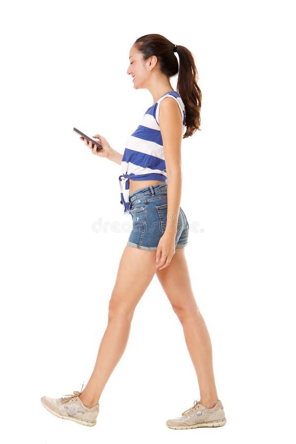 Молодая азиатская женщина идя с мобильным телефоном против изолированной белой предпосылки стоковое фото