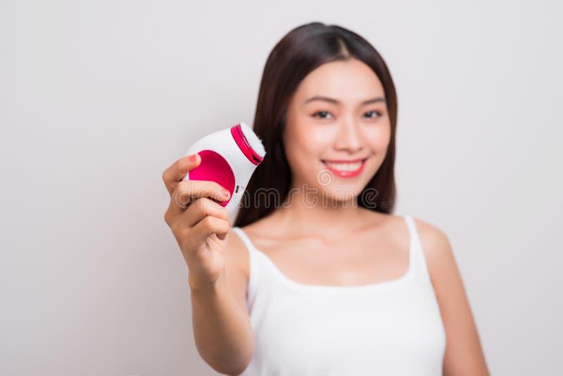 Молодая азиатская женщина использует электрическую щетку для глубоко чистого стоковое фото