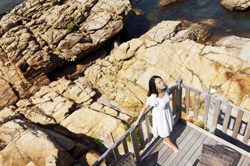 Молодая азиатская женщина наслаждаясь солнечностью стоковые изображения