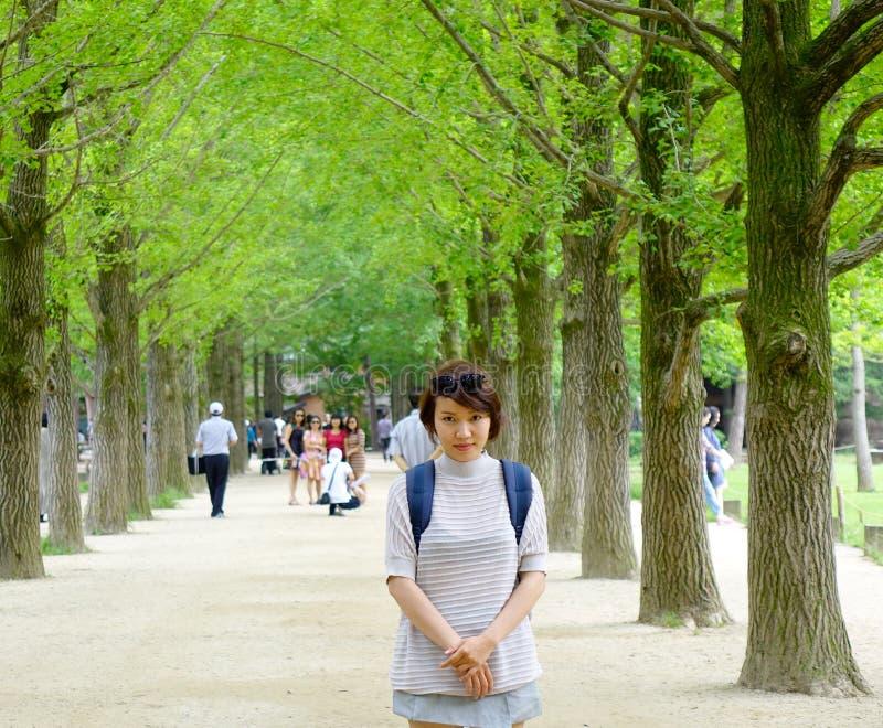Молодая азиатская женщина на парке дерева стоковая фотография