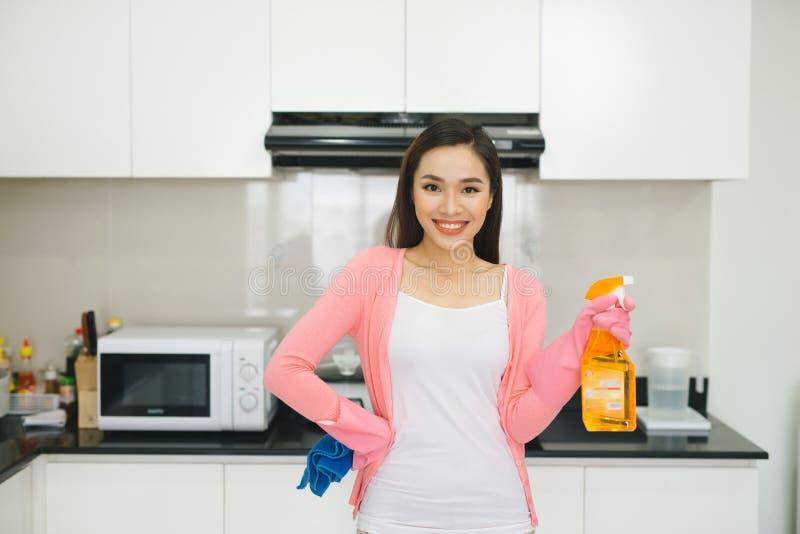 Молодая азиатская женщина подготавливая очистить кухню Рука держа d стоковые изображения