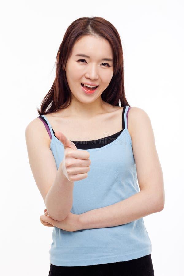 Молодая азиатская женщина показывая большой палец руки. стоковое изображение