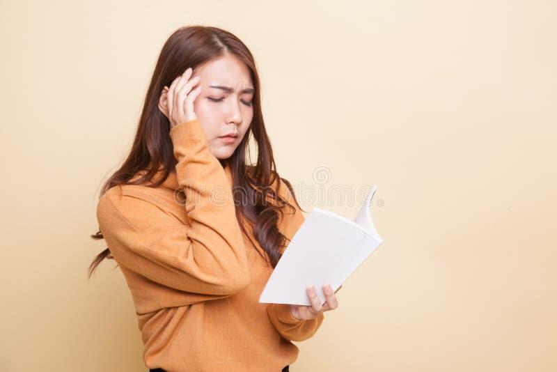 Молодая азиатская женщина полученная головную боль прочитала книгу стоковая фотография rf