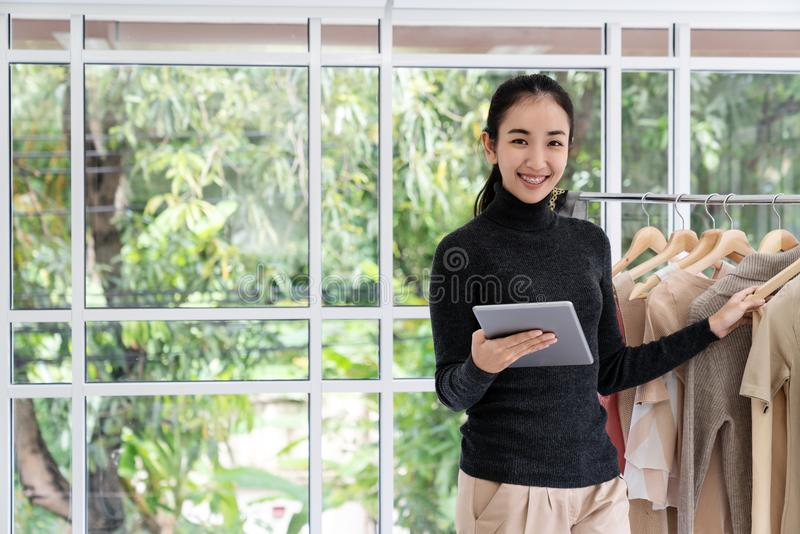 Молодая азиатская женщина предпринимателя используя офис надомного труда таблетки смотря камеру с счастливым вскользь образом жиз стоковые изображения rf