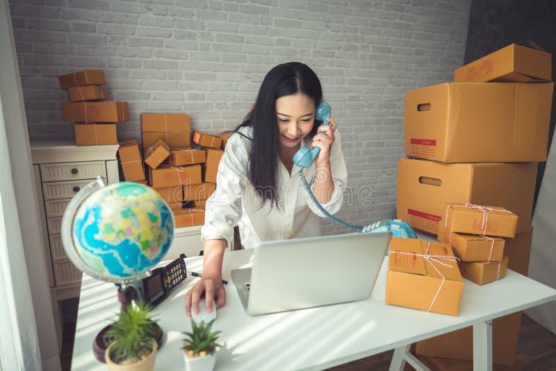 Молодая азиатская женщина работая дома стоковое изображение