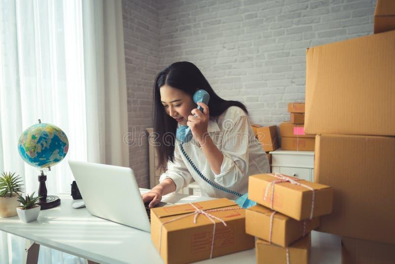 Молодая азиатская женщина работая дома стоковое фото