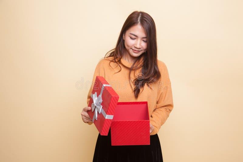 Молодая азиатская женщина раскрывает подарочную коробку стоковое фото rf