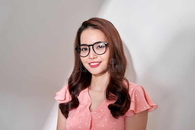 Молодая азиатская женщина со стеклами smiley стороны нося на белой предпосылке стоковое фото rf