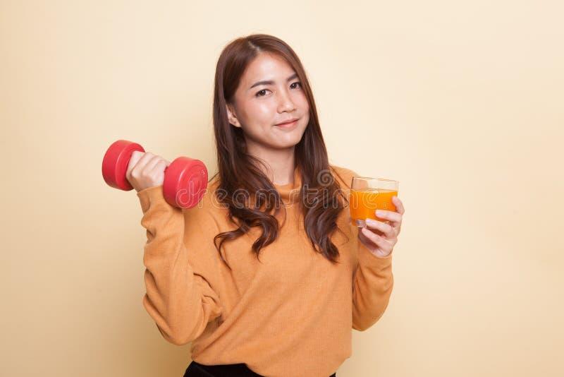 Молодая азиатская женщина с апельсиновым соком питья гантели стоковые фото