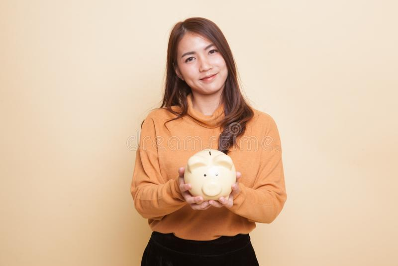 Молодая азиатская женщина с банком монетки свиньи стоковые изображения rf