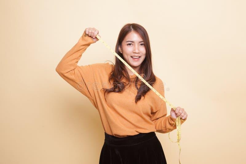 Молодая азиатская женщина с измеряя лентой стоковые фото