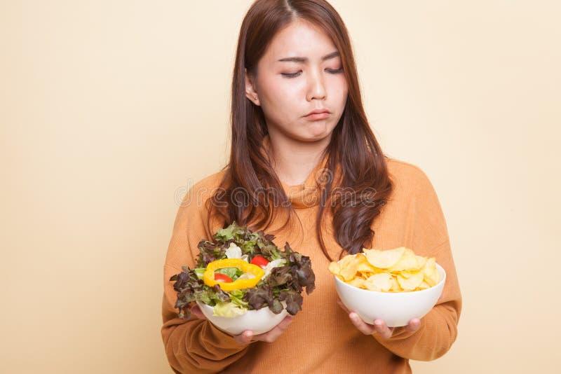 Молодая азиатская женщина с картофельными стружками и салатом стоковое изображение rf