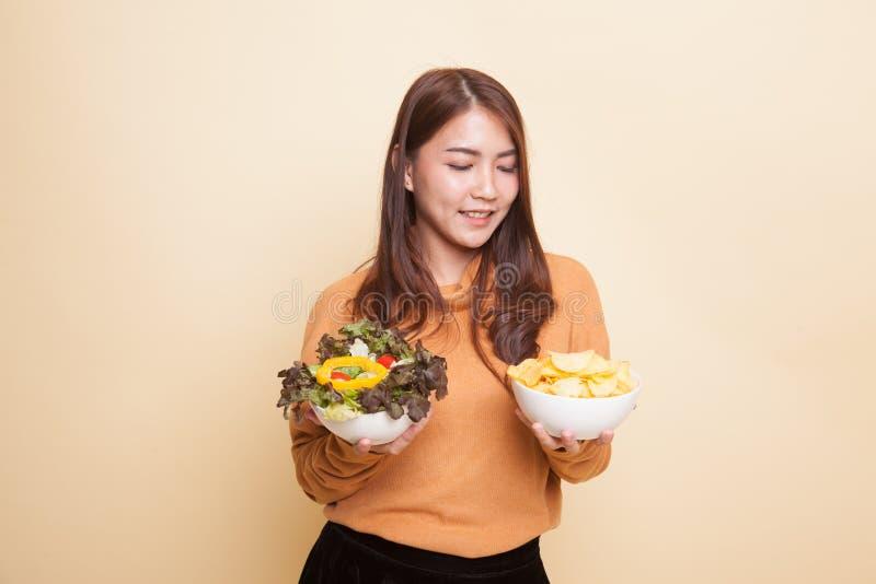 Молодая азиатская женщина с картофельными стружками и салатом стоковые фотографии rf