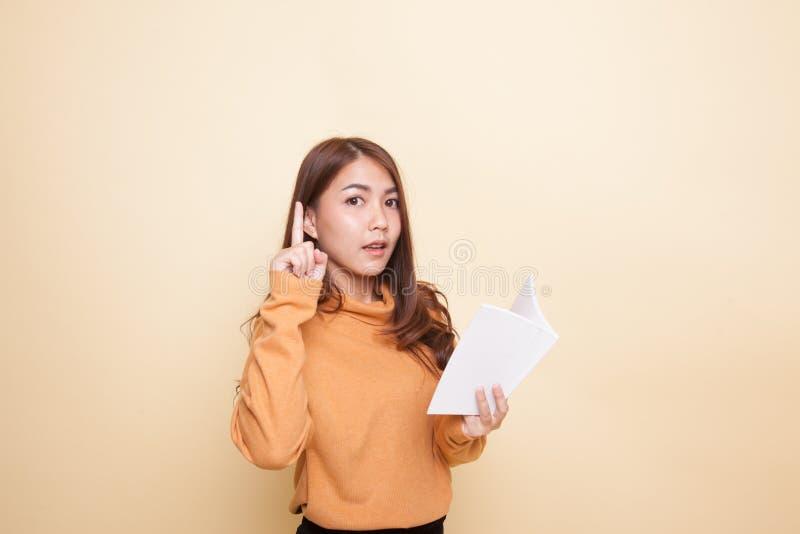 Молодая азиатская женщина с книгой имеет идею стоковая фотография