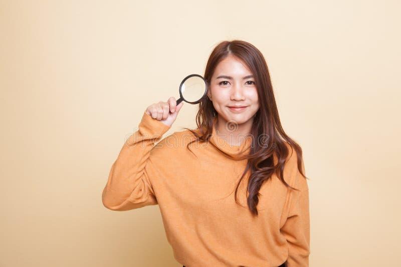 Молодая азиатская женщина с лупой стоковые изображения