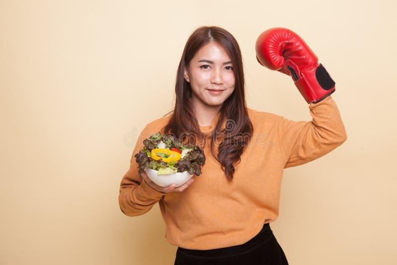 Молодая азиатская женщина с перчаткой и салатом бокса стоковое изображение