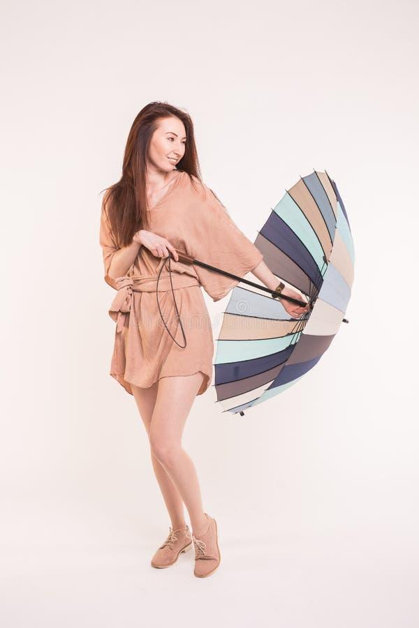 Молодая азиатская женщина с пестротканым зонтиком на белой предпосылке стоковое изображение rf
