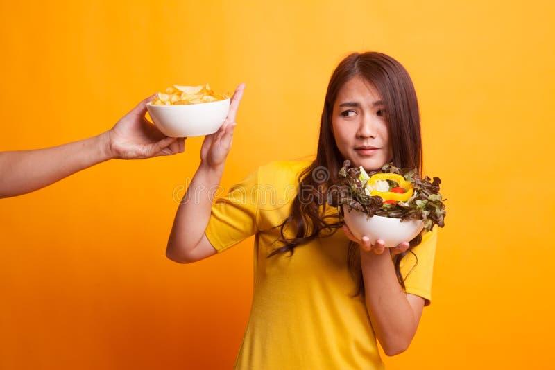 Молодая азиатская женщина с салатом говорит нет к картофельным стружкам в желтом Д-р стоковые изображения rf