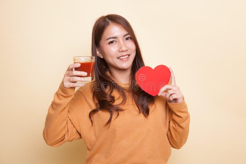 Молодая азиатская женщина с соком томата и красным сердцем стоковая фотография rf