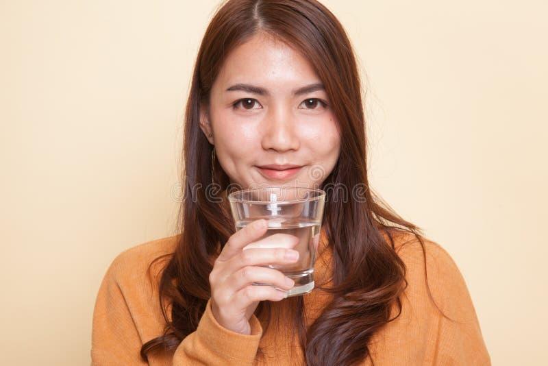 Молодая азиатская женщина с стеклом питьевой воды стоковое фото rf